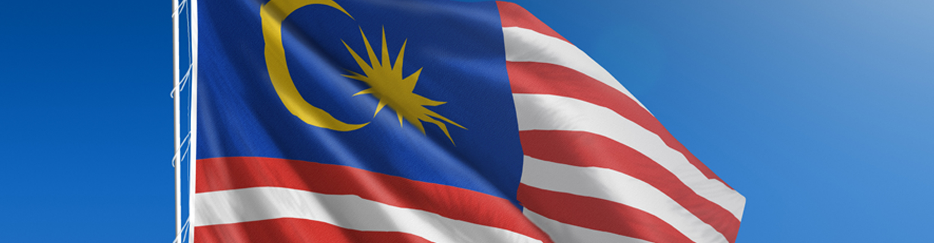 The National flag of Malaysia blowing in the wind in front of a clear blue sky
